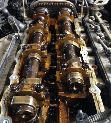 Valve cover removed and camshafts and timing chain exposed. If you look closely at the end of the camshaft on the right you can see that the cut across the shaft doesn't sit in the same alignment as the left camshaft. This is due to the chain having skipped teeth.